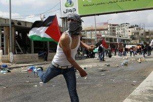 Palestinians throw stones at Israeli troops at Qalandiya checkpoint between Jerusalem and the West Bank city of Ramallah,.