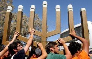 Jewish settlers remove the Menorah from the synagogue in the Netzarim settlement, in the Gaza Strip, August 22, 2005. Israeli troops marched unopposed into the Gaza Strip's last Jewish settlement on Monday to complete the evacuation of the territory after nearly four decades of occupation.  REUTERS/Dan Balilty äåöàú   äîðåøä îáéú äëðñú áðöøéí ìôðé äôéðåé 22.8 ðöøéí áéú ëðñú ôéðåé 05